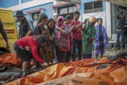 In this Sunday, Dec. 23, 2018, photo, People search for relatives among the bodies of tsunami victims in Carita, Indonesia. The tsunami that hit the coasts of Indonesian islands along the Sunda Strait was not big but it was destructive. The waves smashed onto beaches in the darkness Saturday night without warning, ripping houses and hotels from their foundations in seconds and sweeping terrified concertgoers into the sea. (AP Photo/Fauzy Chaniago)