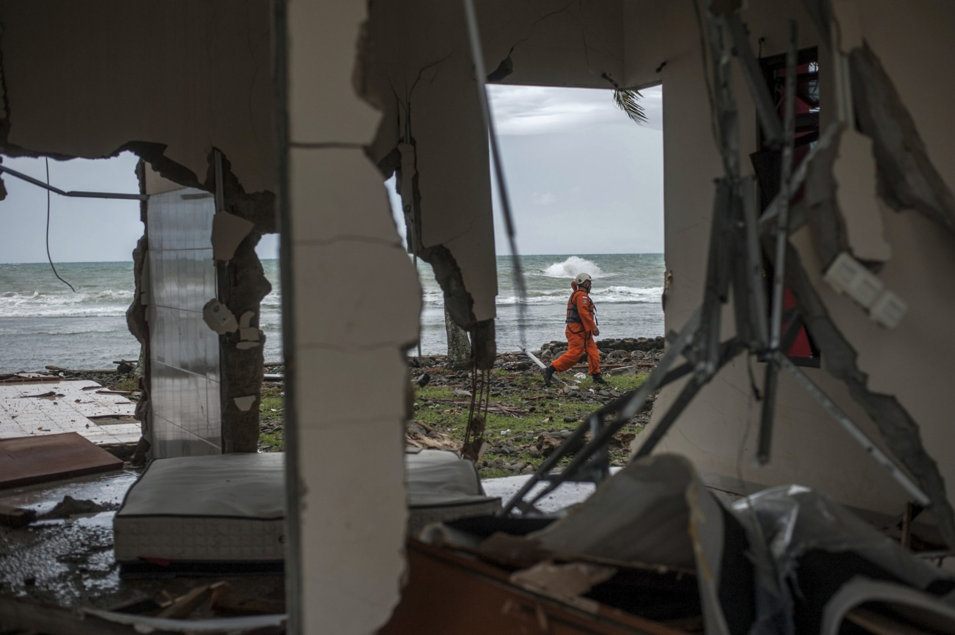 In this Sunday, Dec. 23, 2018, photo, a rescuer is seen through a damaged house as he takes part in a search operation of tsunami victims in Carita, Indonesia. The tsunami that hit the coasts of Indonesian islands along the Sunda Strait was not big but it was destructive. The waves smashed onto beaches in the darkness Saturday night without warning, ripping houses and hotels from their foundations in seconds and sweeping terrified concertgoers into the sea. (AP Photo/Fauzy Chaniago)