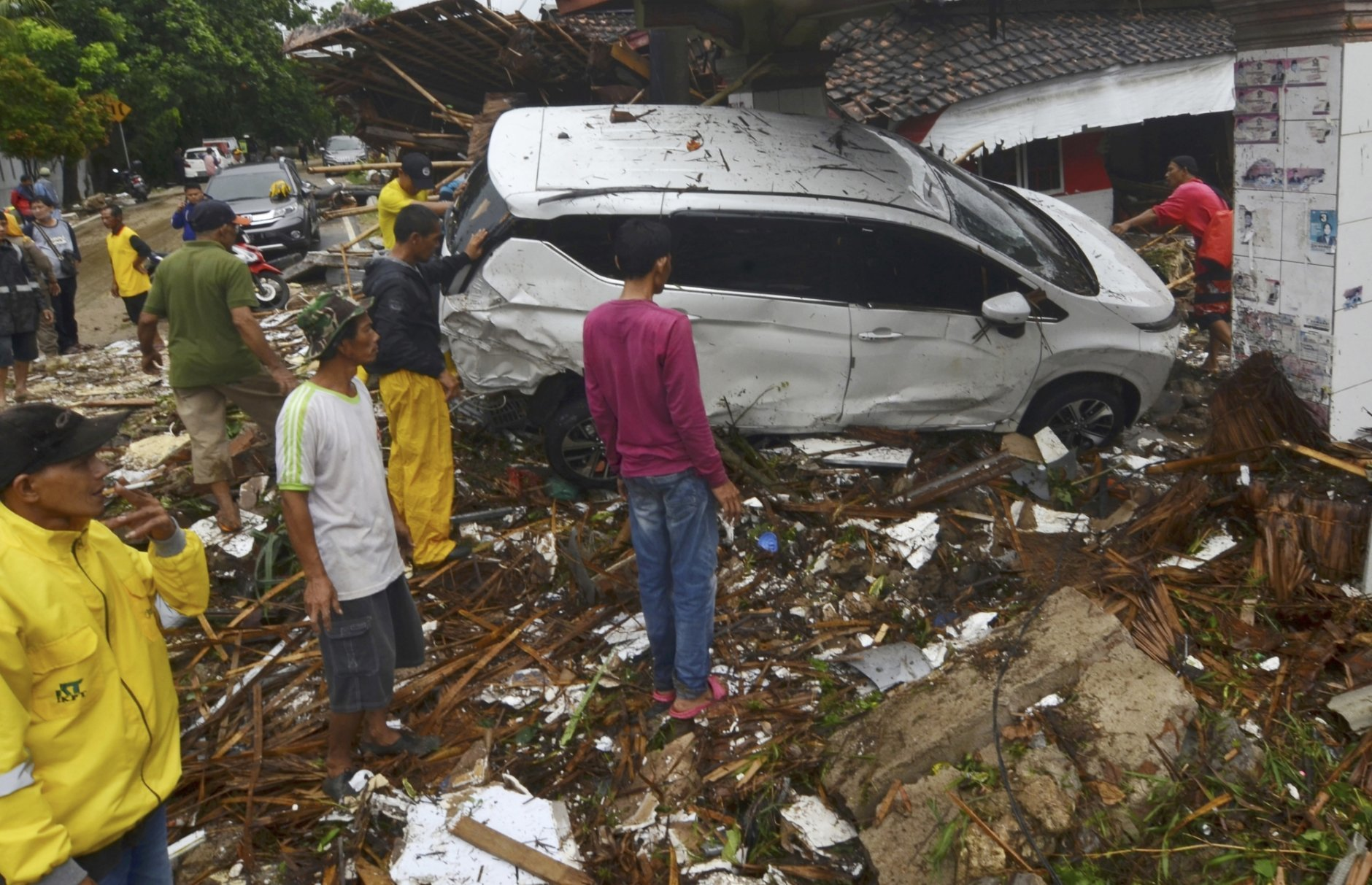 In this Sunday, Dec. 23, 2018, photo, people inspect the wreckage of a car swept away by a tsunami in Carita, Indonesia. The tsunami that hit the coasts of Indonesian islands along the Sunda Strait was not big but it was destructive. The waves smashed onto beaches in the darkness Saturday night without warning, ripping houses and hotels from their foundations in seconds and sweeping terrified concertgoers into the sea. (AP Photo)