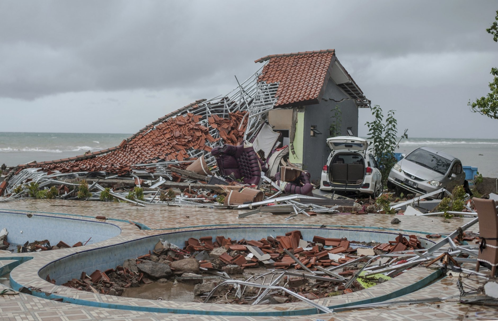 In this Sunday, Dec. 23, 2018, photo, debris littered a property badly damaged by a tsunami in Carita, Indonesia. The tsunami that hit the coasts of Indonesian islands along the Sunda Strait was not big but it was destructive. The waves smashed onto beaches in the darkness Saturday night without warning, ripping houses and hotels from their foundations in seconds and sweeping terrified concertgoers into the sea. (AP Photo/Fauzy Chaniago)