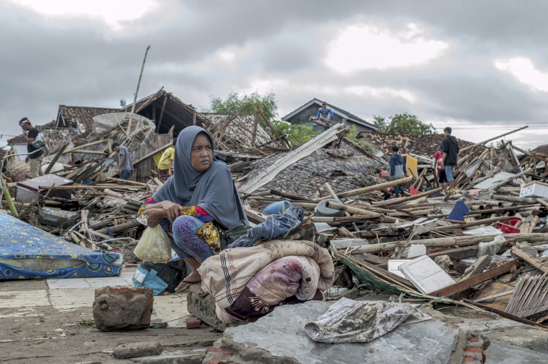 In this Monday, Dec. 24, 2018, photo, a tsunami survivor sits on a pice of debris as she salvages items from the location of her house in Sumur, Indonesia. The tsunami that hit the coasts of Indonesian islands along the Sunda Strait was not big but it was destructive. The waves smashed onto beaches in the darkness Saturday night without warning, ripping houses and hotels from their foundations in seconds and sweeping terrified concertgoers into the sea. (AP Photo/Fauzy Chaniago)