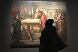 """In this Dec. 3, 2018 photo, a visitor to an exhibition of Tintoretto works looks at his """"Presentation of Jesus in the Temple"""" at the Ducal Palace in Venice. After the show closes in January, it moves to the National Gallery of Art in Washington, D.C., in what would be the first-ever Tintoretto retrospective outside of Europe. (AP Photo/Frances D'Emilio)"""