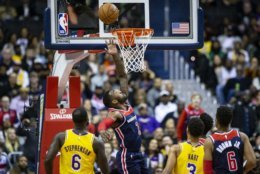 Washington Wizards guard John Wall (2) goes for a layup past Los Angeles Lakers guards Lance Stephenson (6) and Josh Hart (3) as Washington forward Troy Brown Jr. (6) looks on during the first half of an NBA basketball game, Sunday, Dec. 16, 2018, in Washington. (AP Photo/Al Drago)