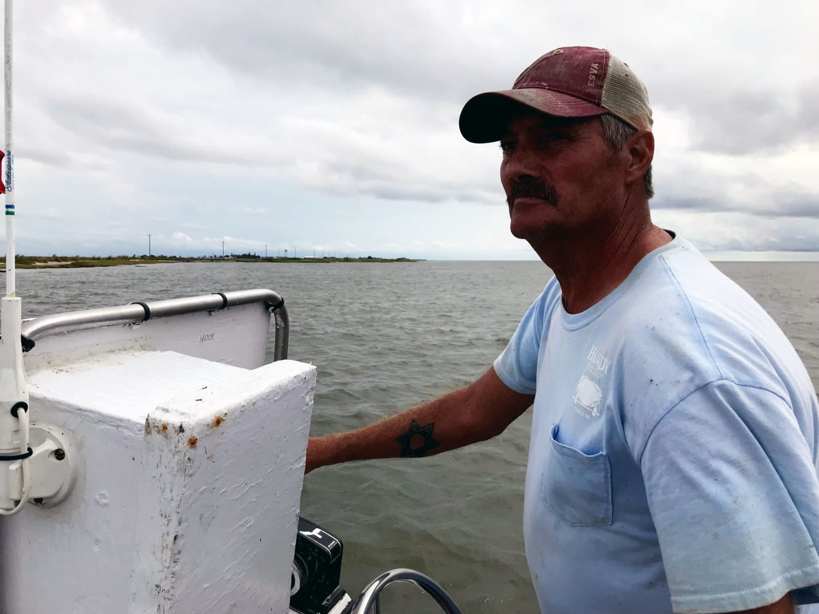Ooker guides his boat near the shore of Uppards.  It's a section of land that used to be connected to the rest of Tangier Island, but today is separated by water. (WTOP/Michelle Basch)