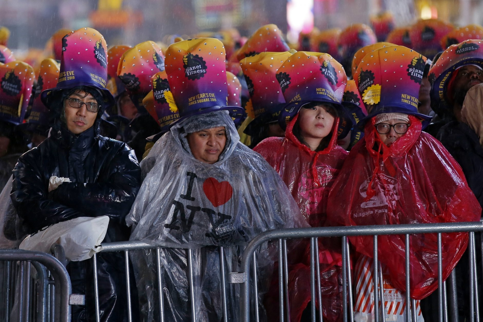 Revelers wait in the rain in New York's Times Square, Monday, Dec. 31, 2018, as they take part in a New Year's Eve celebration. (AP Photo/Adam Hunger)