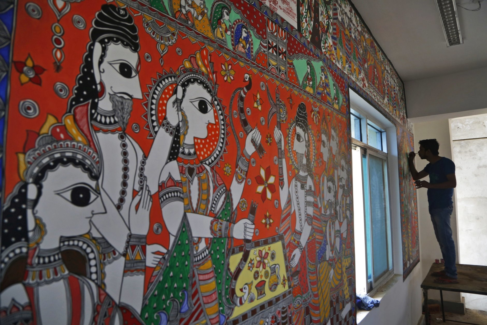 In this Nov. 30, 2018 photo, an Indian artist paints a wall with traditional Mithila art at the newly built Janakpur train station in Nepal from where a new 34 kilometers (21 miles) long rail line runs to Jay Nagar in the Indian state of Bihar. The competition between two Asian giants, India and China, for influence over tiny Nepal is yielding a bonanza in the form of the Himalayan mountain nation's first modern railway, and possibly more to come.(AP Photo/Niranjan Shrestha)