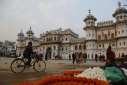 In this Nov. 30, 2018 photo, a Nepalese man rides his bicycle in front of the Ram Janaki temple in Janakpur, Nepal. Millions of Hindu devotees travel every year to the temple where the Hindu goddess Sita is believed to have been born and later married the Hindu god Ram. A new rail line connecting the 34 kilometers (21 miles) between Janakpur in southeastern Nepal and Jay Nagar in the Indian state of Bihar are raising hopes for new business and pilgrimages. (AP Photo/Niranjan Shrestha)