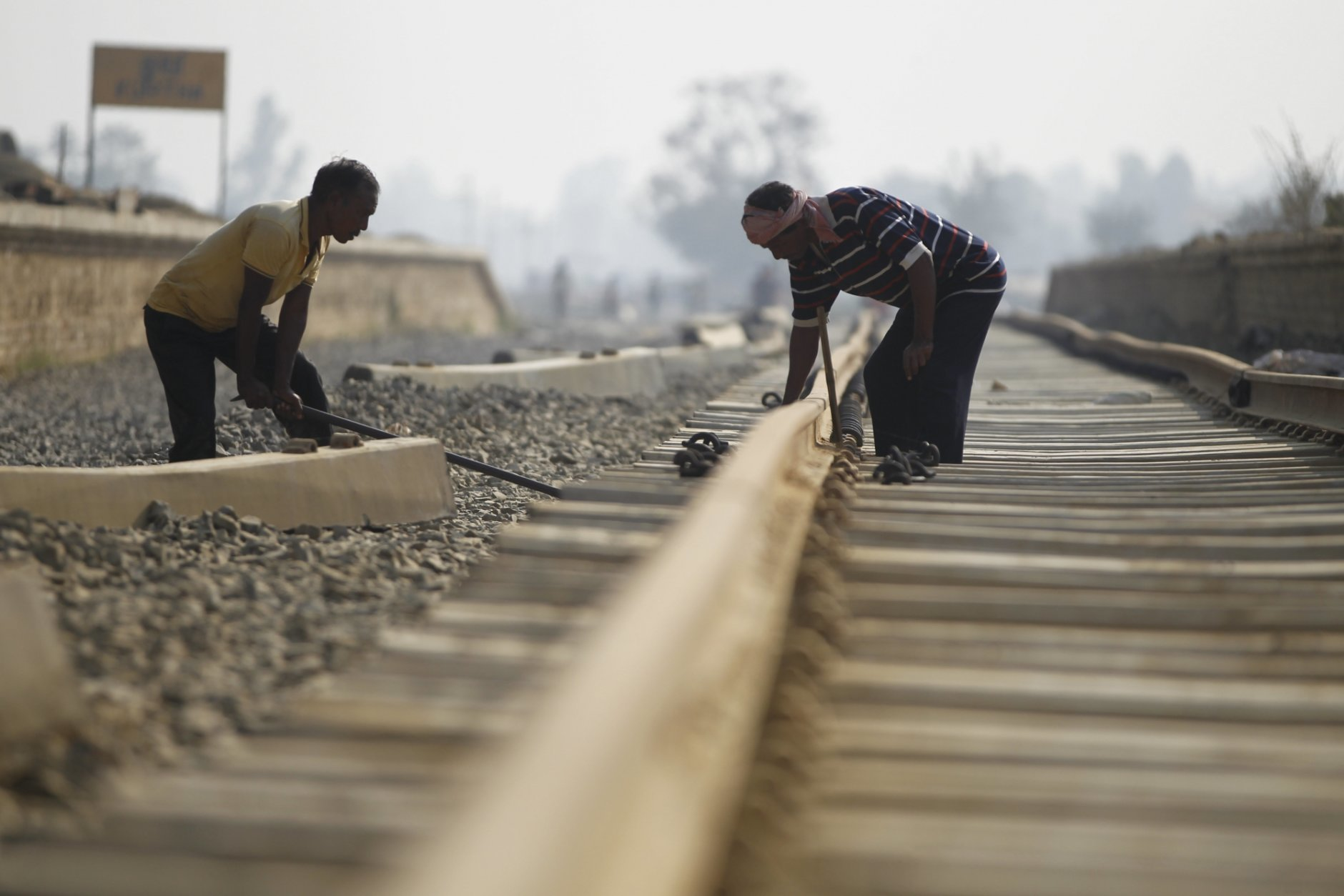 In this Nov. 29, 2018 photo, Nepalese construction laborers work at the terminal train station at Kurtha near Janakpur, Nepal from where a new rail line connects to Jay Nagar in the Indian state of Bihar. The competition between two Asian giants, India and China, for influence over tiny Nepal is yielding a bonanza in the form of the Himalayan mountain nation's first modern railway, and possibly more to come. (AP Photo/Niranjan Shrestha)