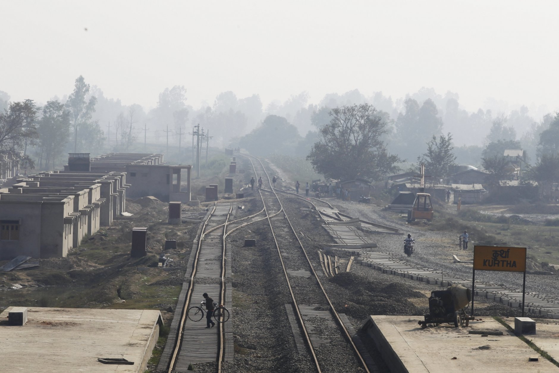 In this Nov. 29, 2018. a Nepalese man carrying his bicycle crosses train tracks at Kurtha near Janakpur, Nepal from where a new rail line connects to Jay Nagar in the Indian state of Bihar. The competition between two Asian giants, India and China, for influence over tiny Nepal is yielding a bonanza in the form of the Himalayan mountain nation's first modern railway, and possibly more to come. (AP Photo/Niranjan Shrestha)(