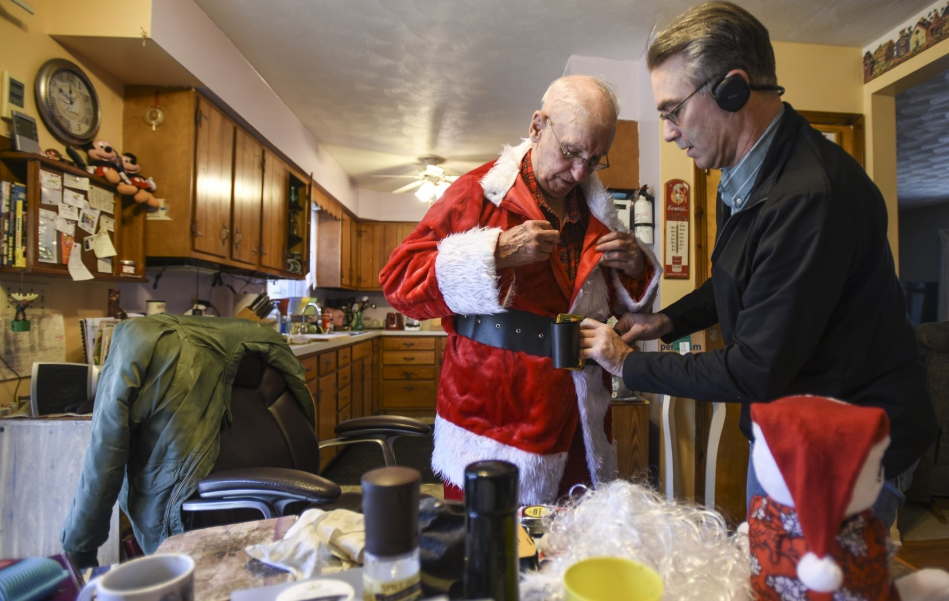In this Saturday, Dec. 8, 2018 photo, Dana West, right, helps his 90-year-old father Don into his Santa suit in Eaton Rapids, Mich. Don is headed to a Charlotte adult foster care home to visit Jackie, his wife of 64 years. (Matthew Dae Smith/Lansing State Journal via AP)