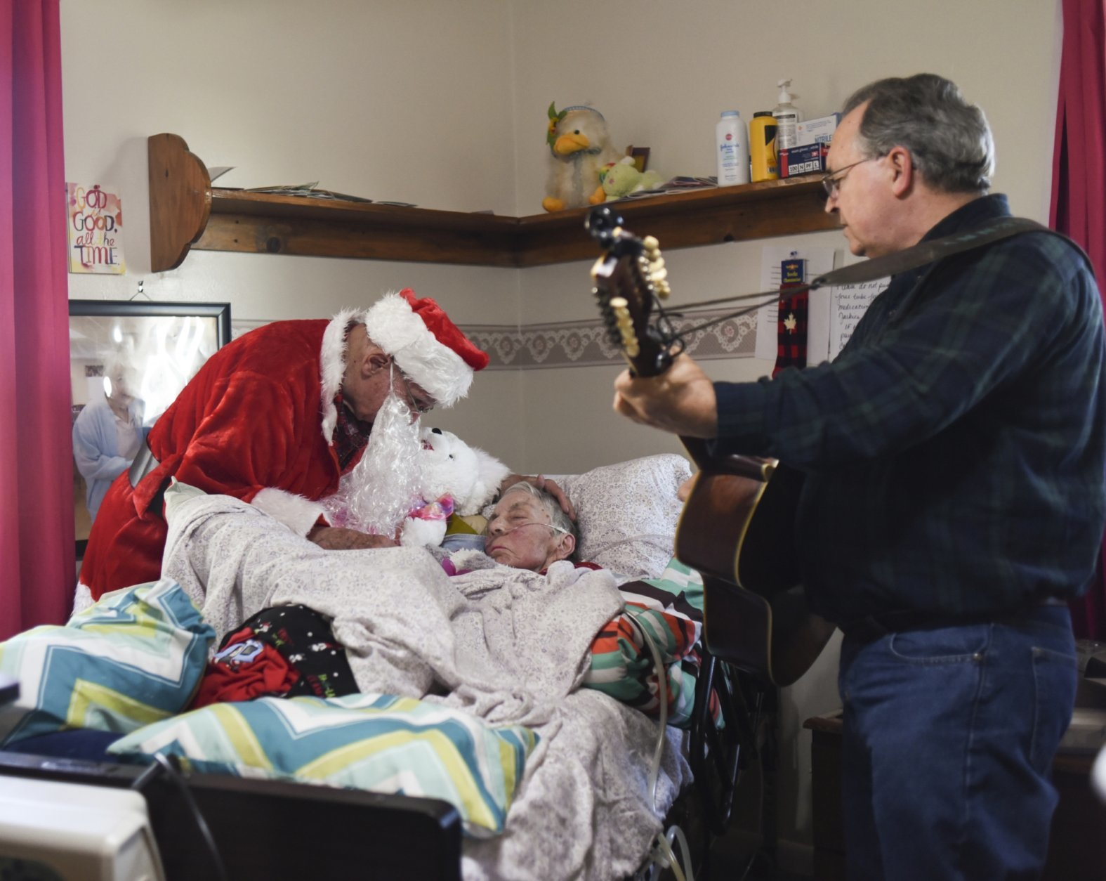 In this Saturday, Dec. 8, 2018 photo, Don West, 90, leans in to kiss his wife Jackie goodnight at Golden Days II Adult Foster Care in Charlotte following a Christmas party for residents and staff at the home. West hired musician Dennis Michaels, right, to play music. (Matthew Dae Smith/Lansing State Journal via AP)