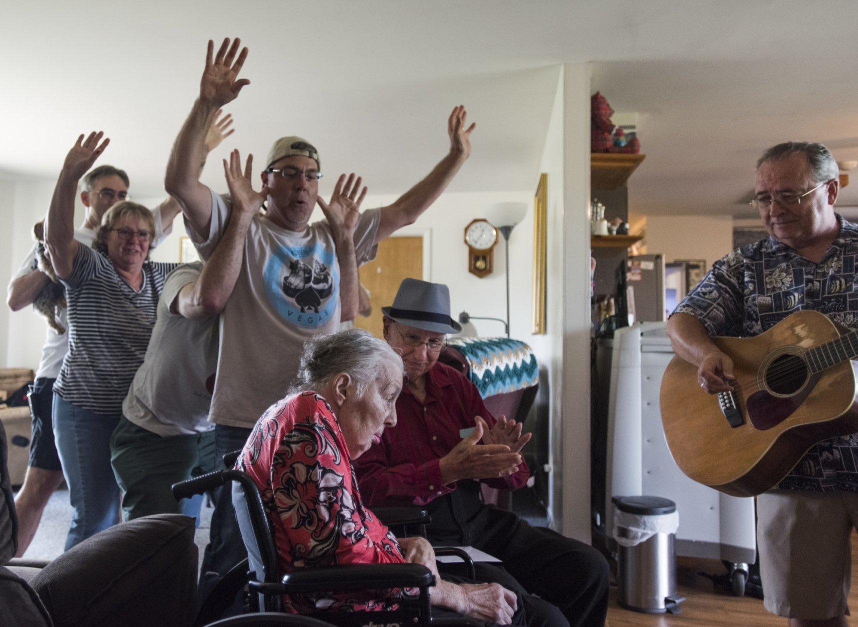 """In this Tuesday, Aug. 21, 2018 photo Don West, center, sings and claps along to the song """"You are my Sunshine,""""  at Golden Days II Adult Foster Care nursing home in Charlotte, Mich., as friends and family dance behind them. His wife Jackie had a stroke in June of 2017 and has been at the home since. (Matthew Dae Smith/Lansing State Journal via AP)"""