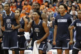 Old Dominion's Jason Wade, center, cheers with teammates on the bench in the final seconds of an NCAA college basketball game against Syracuse in Syracuse, N.Y., Saturday, Dec. 15, 2018. Old Dominion won 68-62. (AP Photo/Nick Lisi)