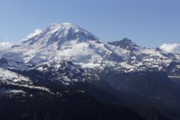 FILE - In this file photo taken June 19, 2013, Mount Rainier is seen from a helicopter flying south of the mountain and west of Yakima, Wash. Access to Mount Rainier National Park and other national parks will be limited due to the government shutdown. (AP Photo/Elaine Thompson, File)