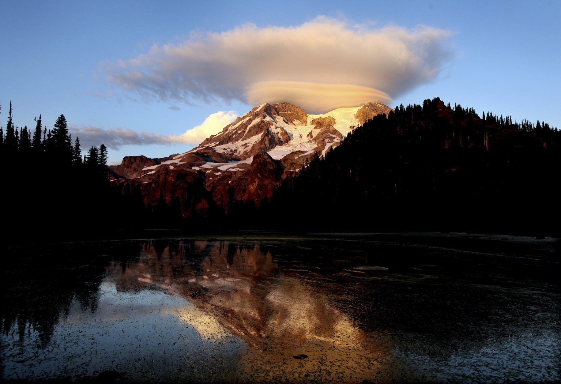 FILE - In this September 2012 file photo, a cloud hovers over Mount Rainier at sunset in a view from Klapatche Park Camp at Mount Rainier National Park, Wash. Access to Mount Rainer National Park and other national parks will be limited due to the government shutdown. (Drew Perine/The News Tribune via AP, File)
