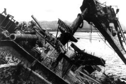 FILE - In this May 24, 1943 file photo, the capsized battleship USS Oklahoma is lifted out of the water at Pearl Harbor in Honolulu, Hawaii. More than 75 years after nearly 2,400 members of the U.S. military were killed in the Japanese attack at Pearl Harbor, some who died on Dec. 7, 1941, are finally being laid to rest in cemeteries across the United States. After DNA allowed the men to be identified and returned home, their remains are being buried in places such as Traer, Iowa and Ontonagon, Michigan. (AP Photo, File)