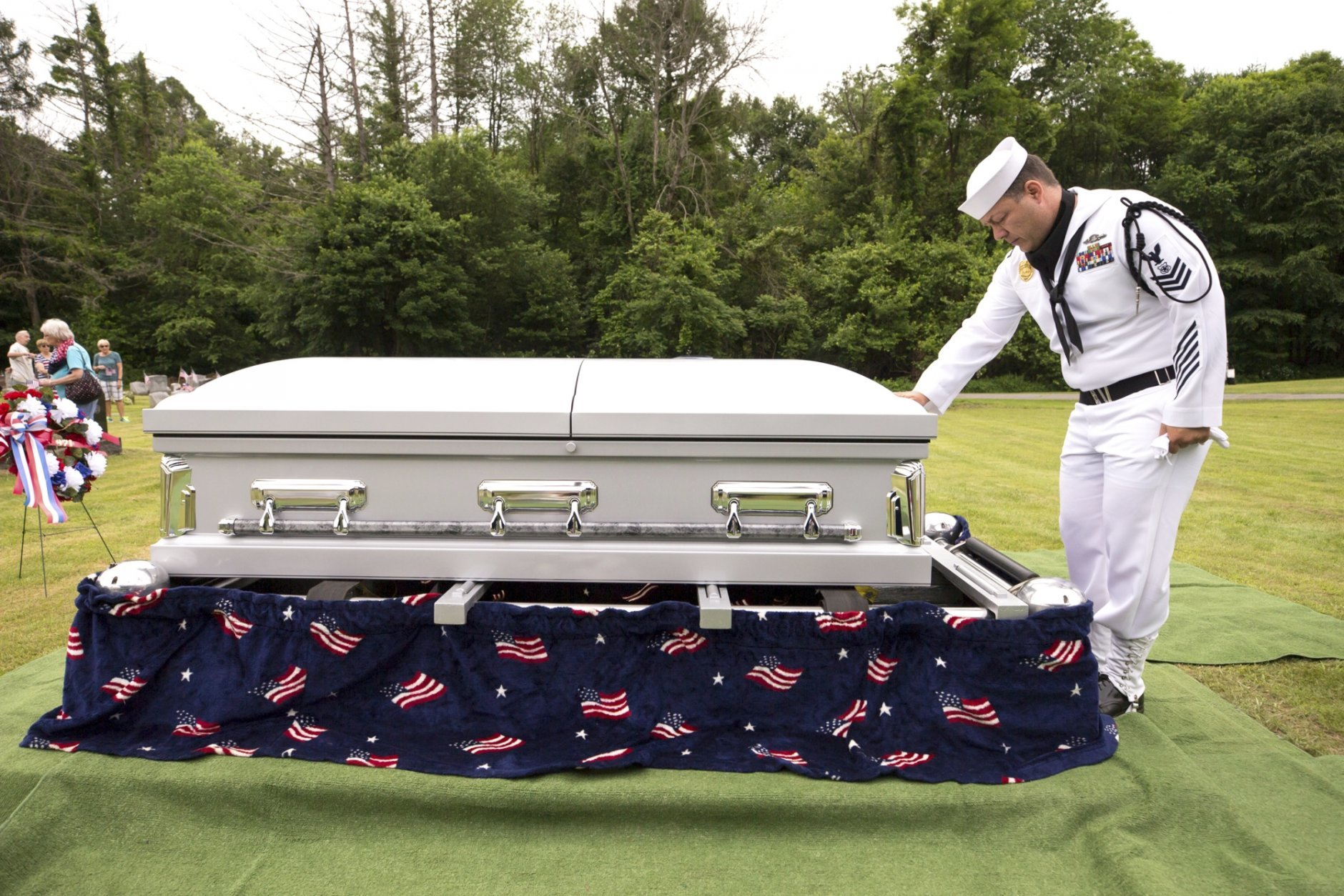 FILE  - In this June 9, 2018, file photo, U.S. Navy Master at Arms First Class Robert Linke, a Los Angeles native stationed at Naval Weapons Station Earle in Colts Neck, N.J., pauses at the casket of U.S. Navy Seaman 1st Class Edward Slapikas, a Newport Township, Pa., native killed while serving aboard the USS Oklahoma in the attack on Pearl Harbor in Dec. 1941, at St. Mary's Cemetery in Nanticoke, Pa. Slapikas' remains were identified earlier this year and returned to Luzerne County for burial 77 years after his death.  (Christopher Dolan/The Citizens' Voice via AP, File)