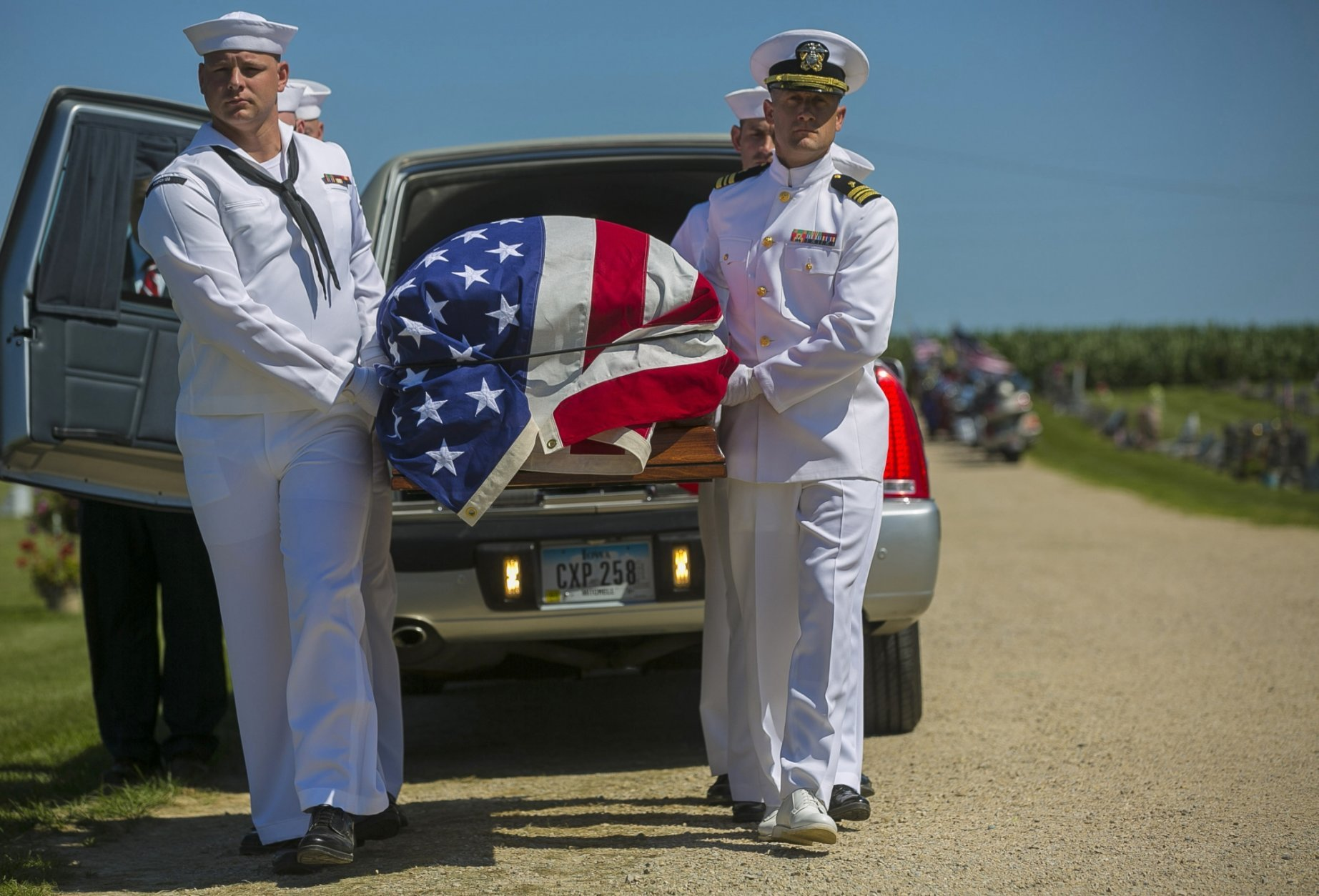FILE - In this July 7, 2018 file photo, U.S. Navy sailors remove the casket with the remains of Seaman First Class Leon Arickx from a hearse at Sacred Heart Cemetery where they will be put to rest in Osage, Iowa. Arickx' remains, which were unidentifiable after his death after the Japanese attack at Pearl Harbor in 1941, were identified through DNA testing earlier this year. More than three-quarters of a century after the devastating attack killed nearly 2,400 in Hawaii, the bodies of some sailors killed at Pearl Harbor are finally being laid to rest. (Chris Zoeller/Globe-Gazette via AP, File)