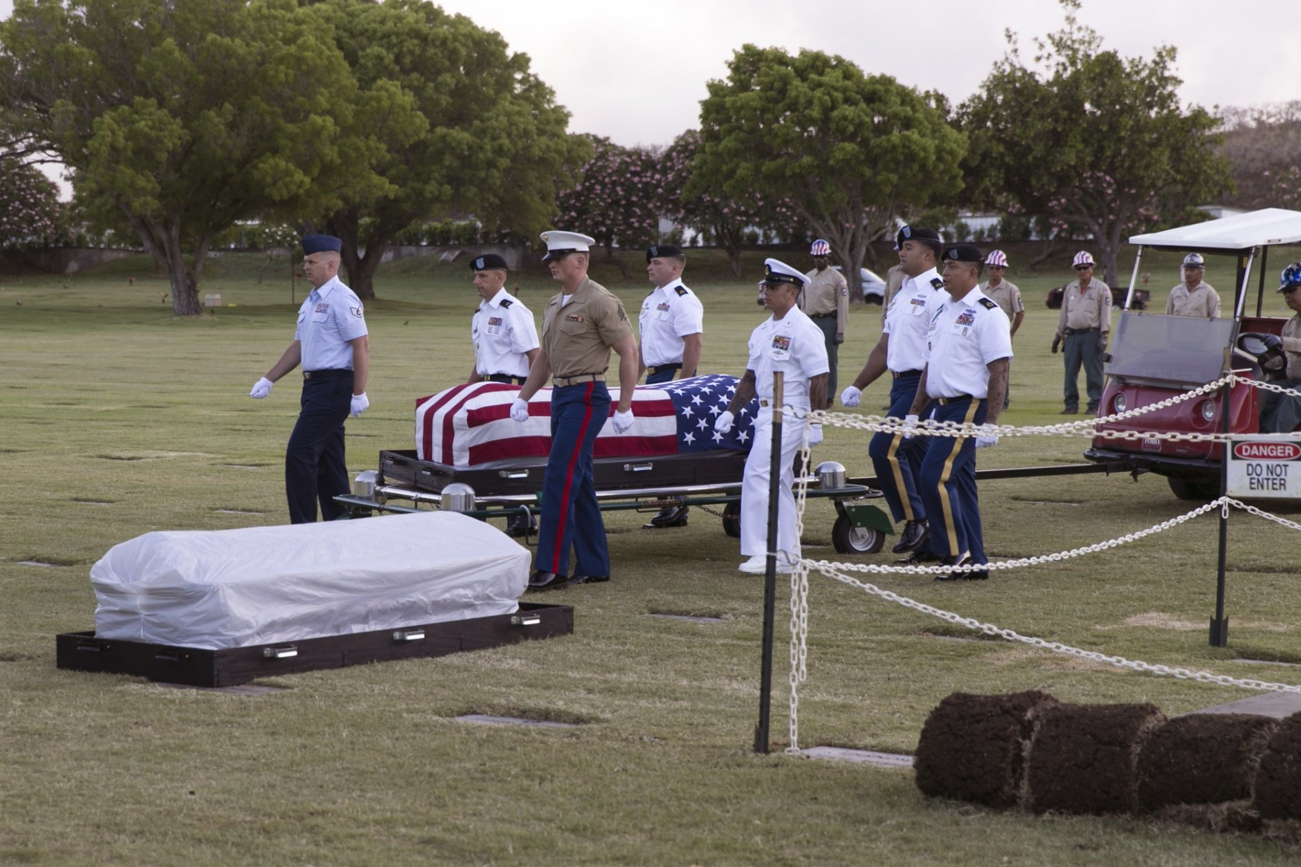 FILE - In this July 27, 2015 file photo, military pallbearers escort the exhumed remains of unidentified crew members of the USS Oklahoma killed in the 1941 bombing of Pearl Harbor that were disinterred from a gravesite at the National Memorial Cemetery of the Pacific in Honolulu. More than 75 years after the Japanese attack killed nearly 2,400 in Hawaii, the bodies of some sailors killed at Pearl Harbor are finally being laid to rest in their hometowns across the U.S. After DNA allowed the men to be identified and returned home, their remains are being buried in places such as Traer, Iowa and Ontonagon, Michigan.  (AP Photo/Marco Garcia, File)