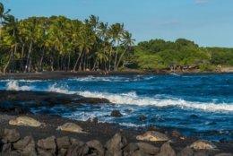 The charcoal-hued beach boasts plenty of vivid scenery. Cross the beach to find a section of the 175-mile Ala Kahakai Trail. (Shutterstock via CNN)