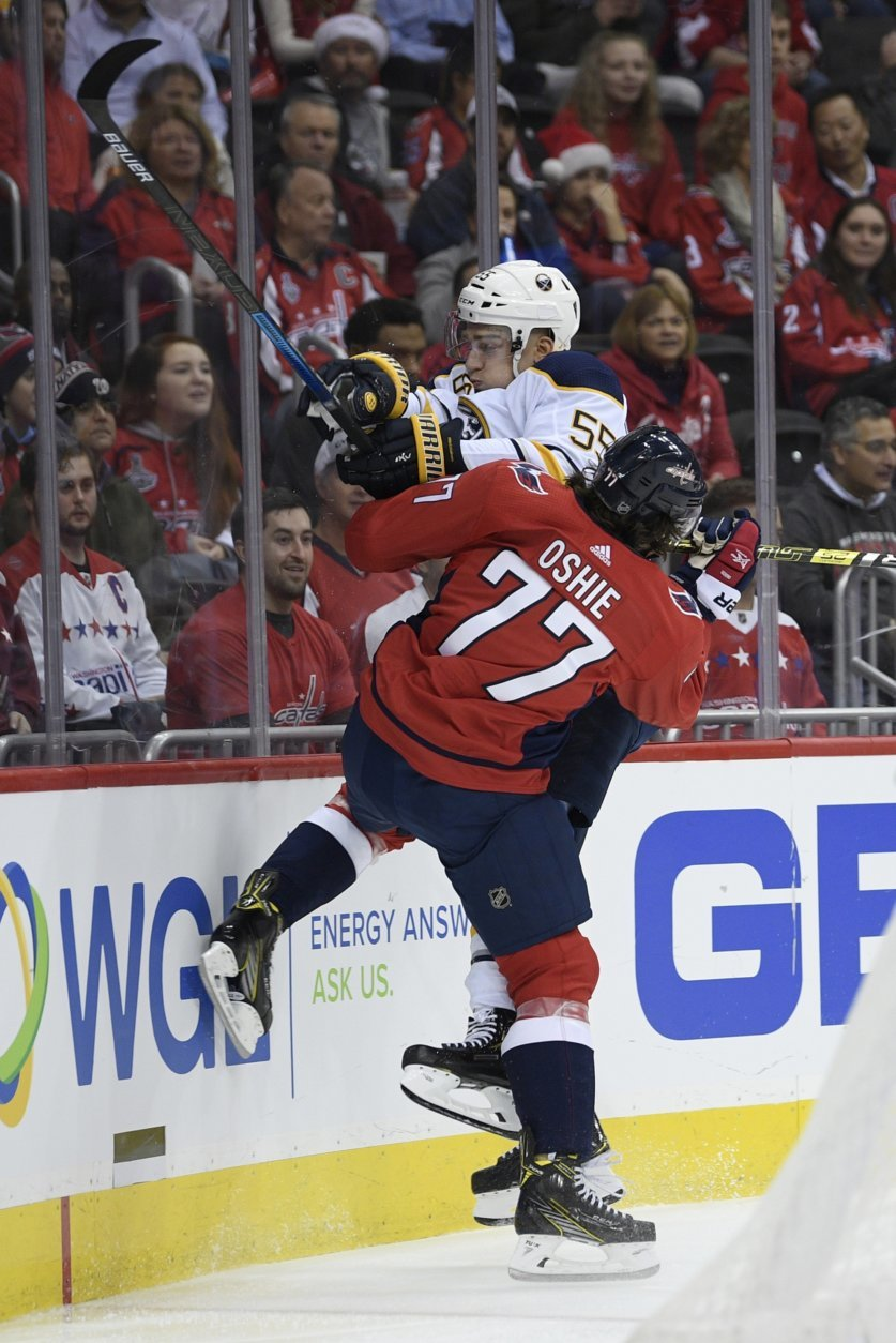 Washington Capitals right wing T.J. Oshie (77) collides with Buffalo Sabres defenseman Rasmus Ristolainen (55), of Finland, during the first period of an NHL hockey game, Friday, Dec. 21, 2018, in Washington. (AP Photo/Nick Wass)