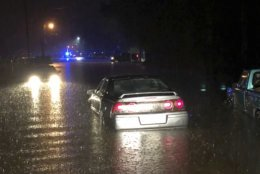 In this photo provided by the Hattiesburg Police Department, released drivers attempt to drive through flash flood waters on Providence Street in Hattiesburg, Miss., Thursday, Dec. 27, 2018. A storm system dumped up to 12 inches of rain in Louisiana and Mississippi, Thursday afternoon through early Friday morning. (Ryan Moore/Hattiesburg Police Department via AP)