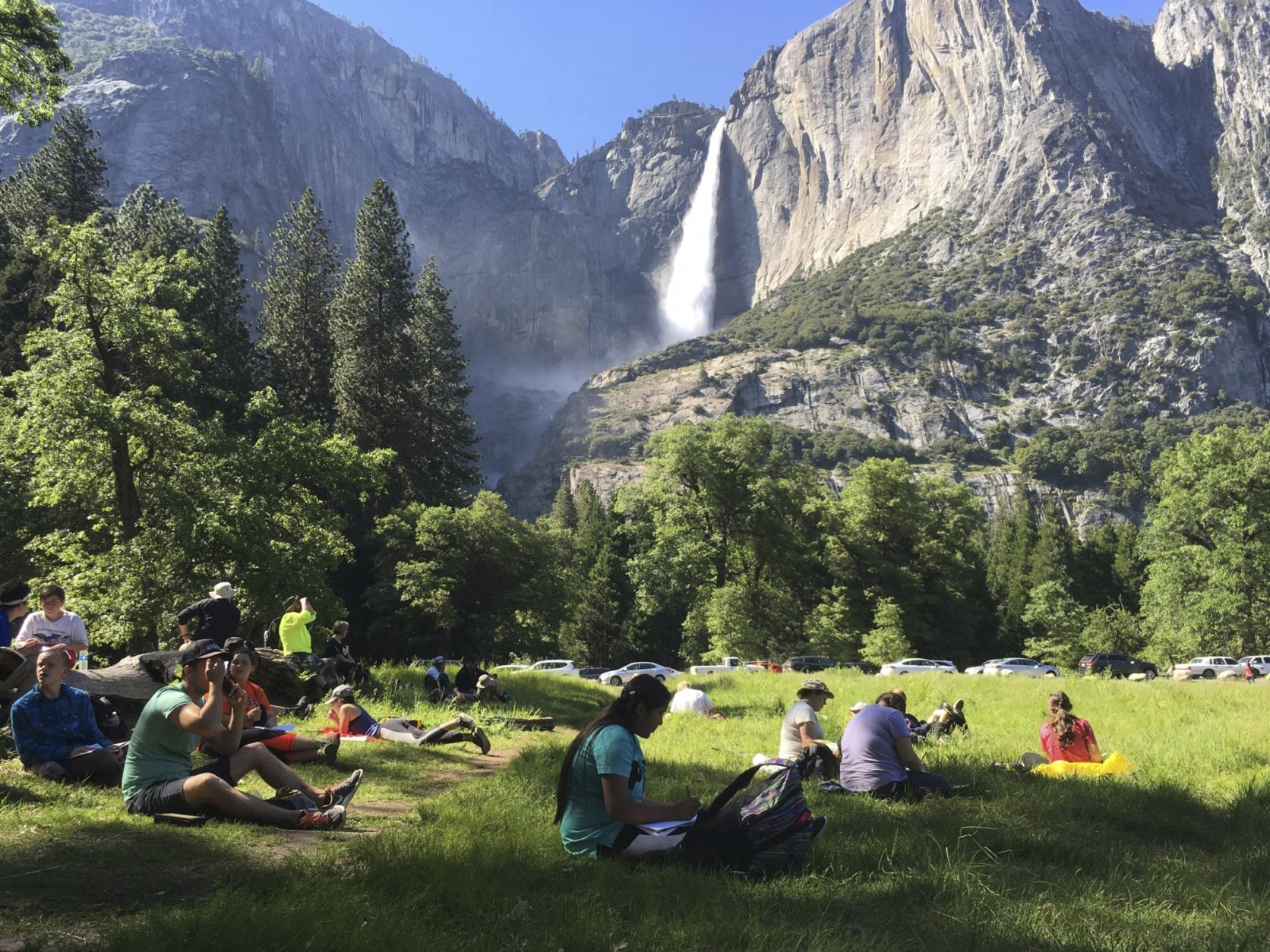 FILE - In this May 25, 2017 file photo, a class of eighth-grade students and their chaperones sit in a meadow at Yosemite National Park, Calif., below Yosemite Falls. Some of the West's iconic national parks are beginning to partially close as they deal with overflowing restrooms and vandals on the 10th day of a federal government shutdown. (AP Photo/Scott Smith, File)