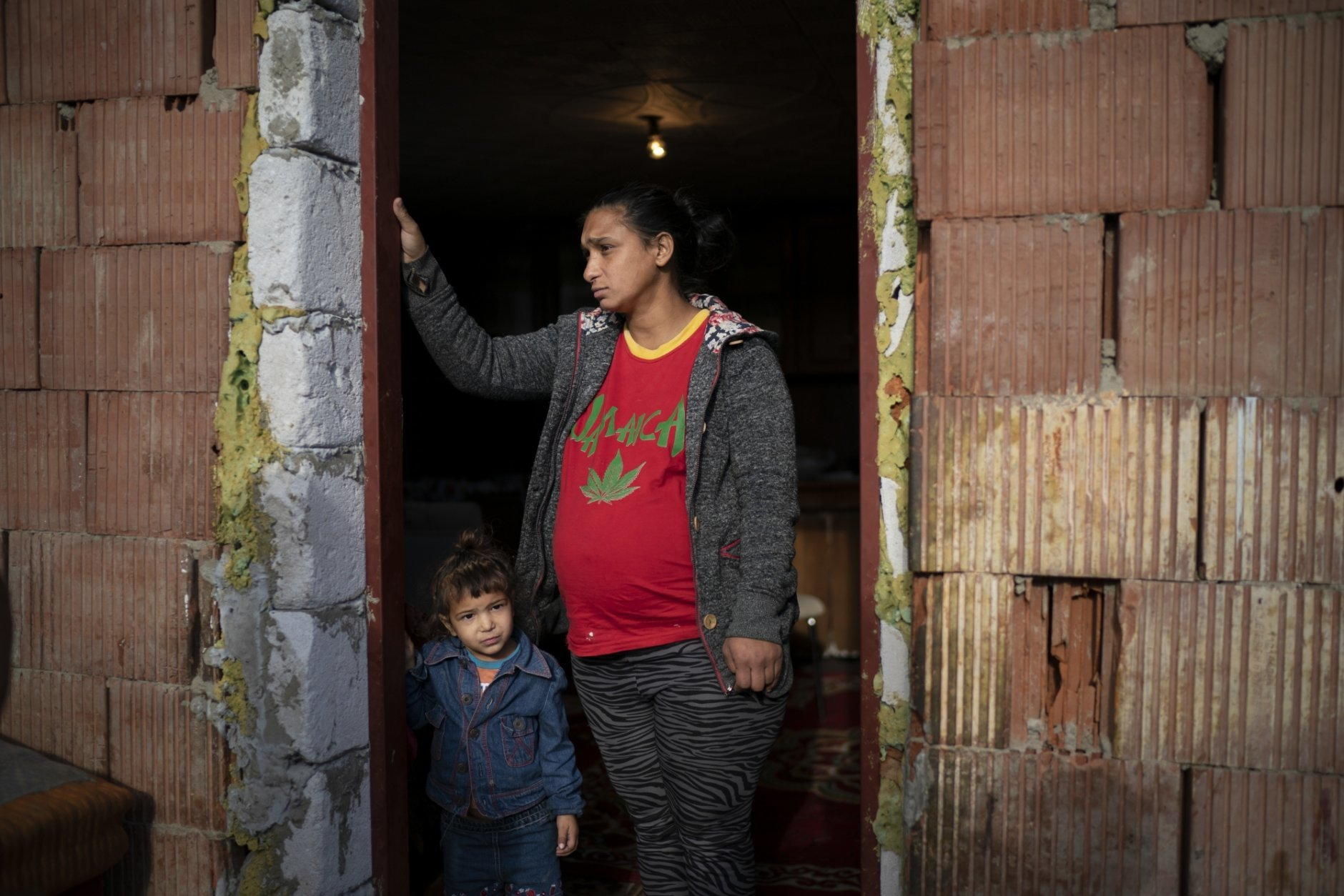 In this Nov. 14, 2018, photo, Jarmila Noskova, 33, stands at the entrance of her house with her daughter in Podhorany village near Kezmarok, Slovakia. Noskova, a Roma woman now pregnant with her seventh child, said she cried for days every time she was forced to remain in the hospital after birth, terrified the hospital would alert the police if she left. (AP Photo/Felipe Dana)