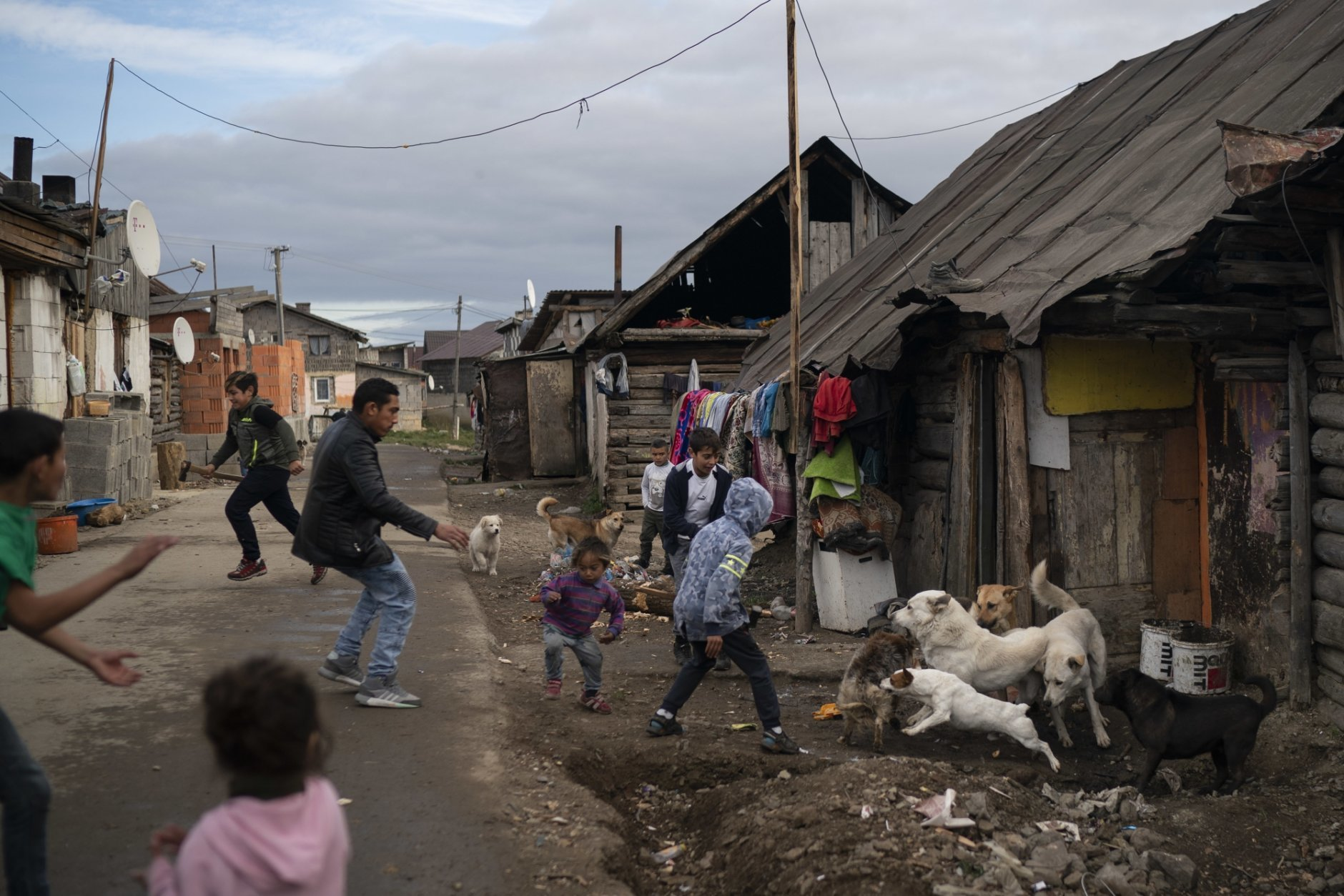 In this Nov. 12, 2018, photo, people run during a dog fight in a village near Kezmarok, Slovakia. An investigation by The Associated Press has found that women and their newborns in Slovakia are routinely, unjustifiably and illegally detained in hospitals across the European Union country. (AP Photo/Felipe Dana)