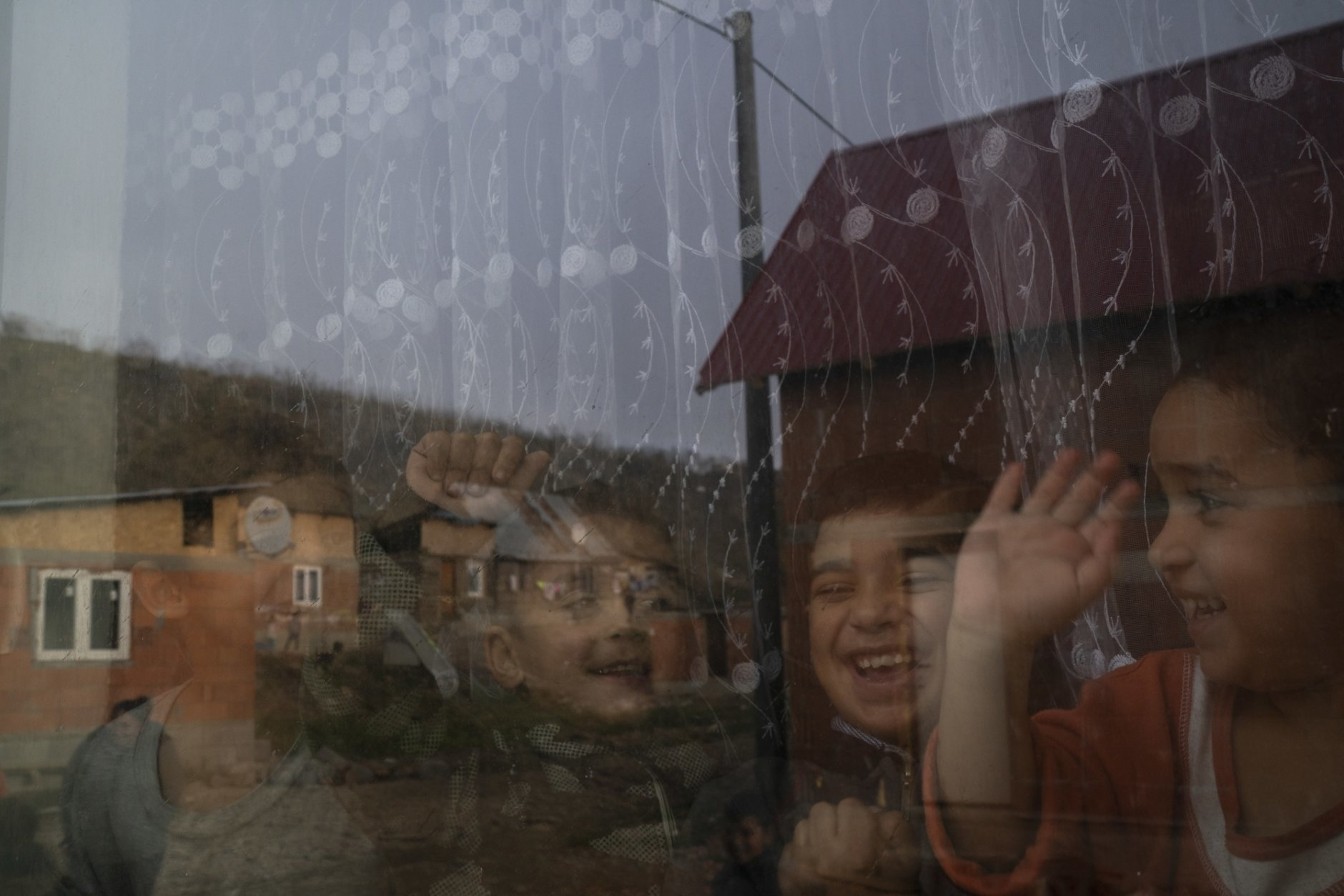 In this Nov. 14, 2018, photo, homes are reflected off the window of Monika Krcova's house as her grandchildren play inside at the Podhorany village near Kezmarok, Slovakia. Krcova did not want to follow the official guidelines and remain in the hospital for four days after her third baby's birth. And so she escaped. Slovakia's Ministry of Health recommends four-day stays for mothers and babies, regardless of their health. Many hospitals seeking insurance reimbursements have turned that into a mandate. (AP Photo/Felipe Dana)