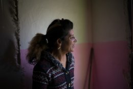 In this Nov. 14, 2018, photo, Monika Krcova talks to a neighbor while standing in her house at the Podhorany village near Kezmarok, Slovakia. Krcova did not want to follow the official guidelines and remain in the hospital for four days after her third baby's birth. And so she escaped. Slovakia's Ministry of Health recommends four-day stays for mothers and babies, regardless of their health. Many hospitals seeking insurance reimbursements have turned that into a mandate. (AP Photo/Felipe Dana)