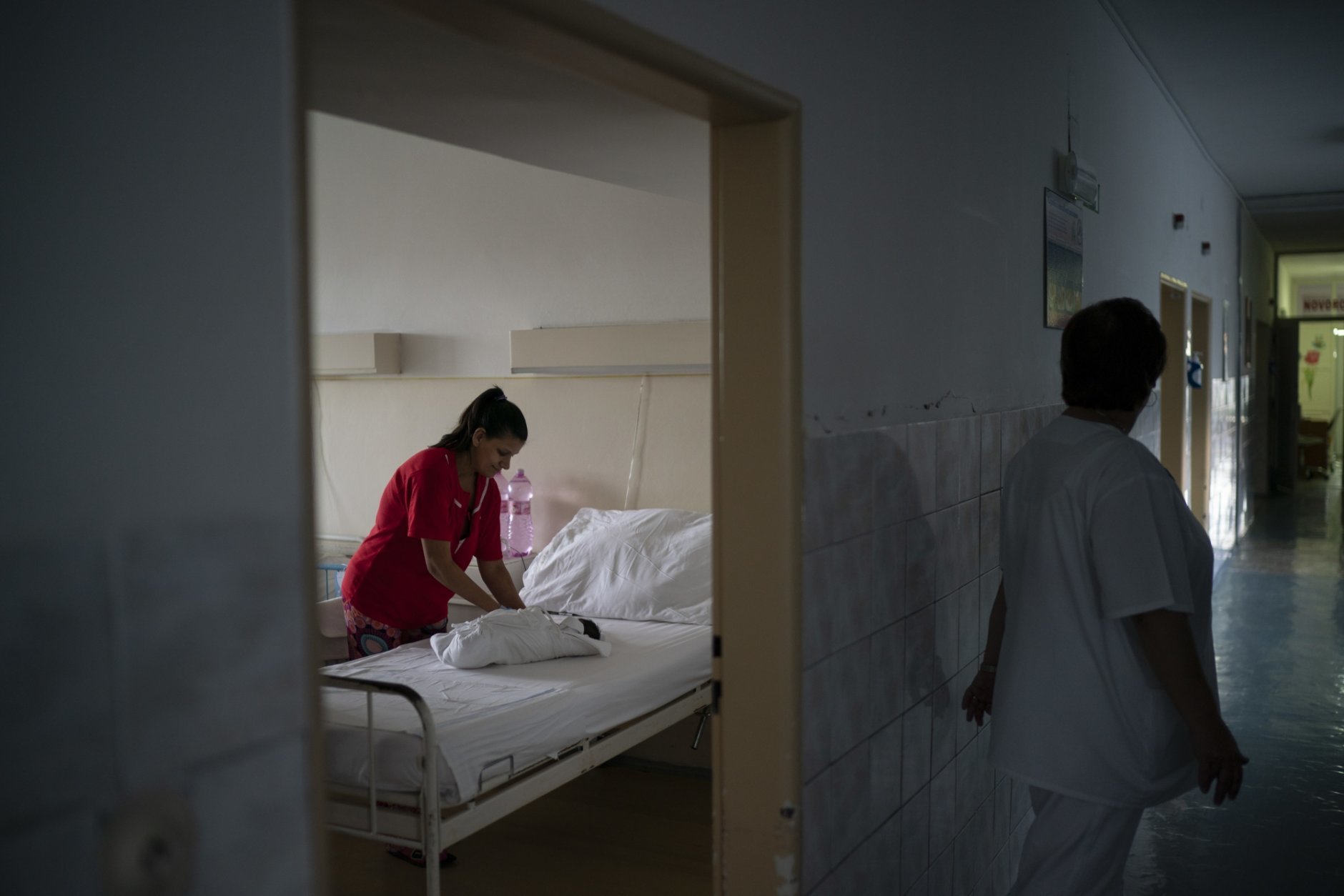In this Nov. 15, 2018, photo, a nurse stands outside the room as Paulina Balazova prepares the clothes of her newborn baby at a hospital in Trebisov, Slovakia. An investigation by The Associated Press has found that women and their newborns in Slovakia are routinely, unjustifiably and illegally detained in hospitals across the European Union country. (AP Photo/Felipe Dana)