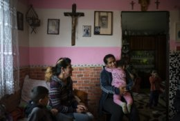 In this Nov. 14, 2018, photo, Monika Krcova, center left, sits with her daughter Ivana and her grandchildren in their house in Podhorany village, near Kezmarok, Slovakia. Krcova is no longer afraid of her local hospital since she isn't planning to have more children, but worries about her daughter Ivana, who says she also was slapped by nurses when she previously gave birth and is now pregnant. (AP Photo/Felipe Dana)