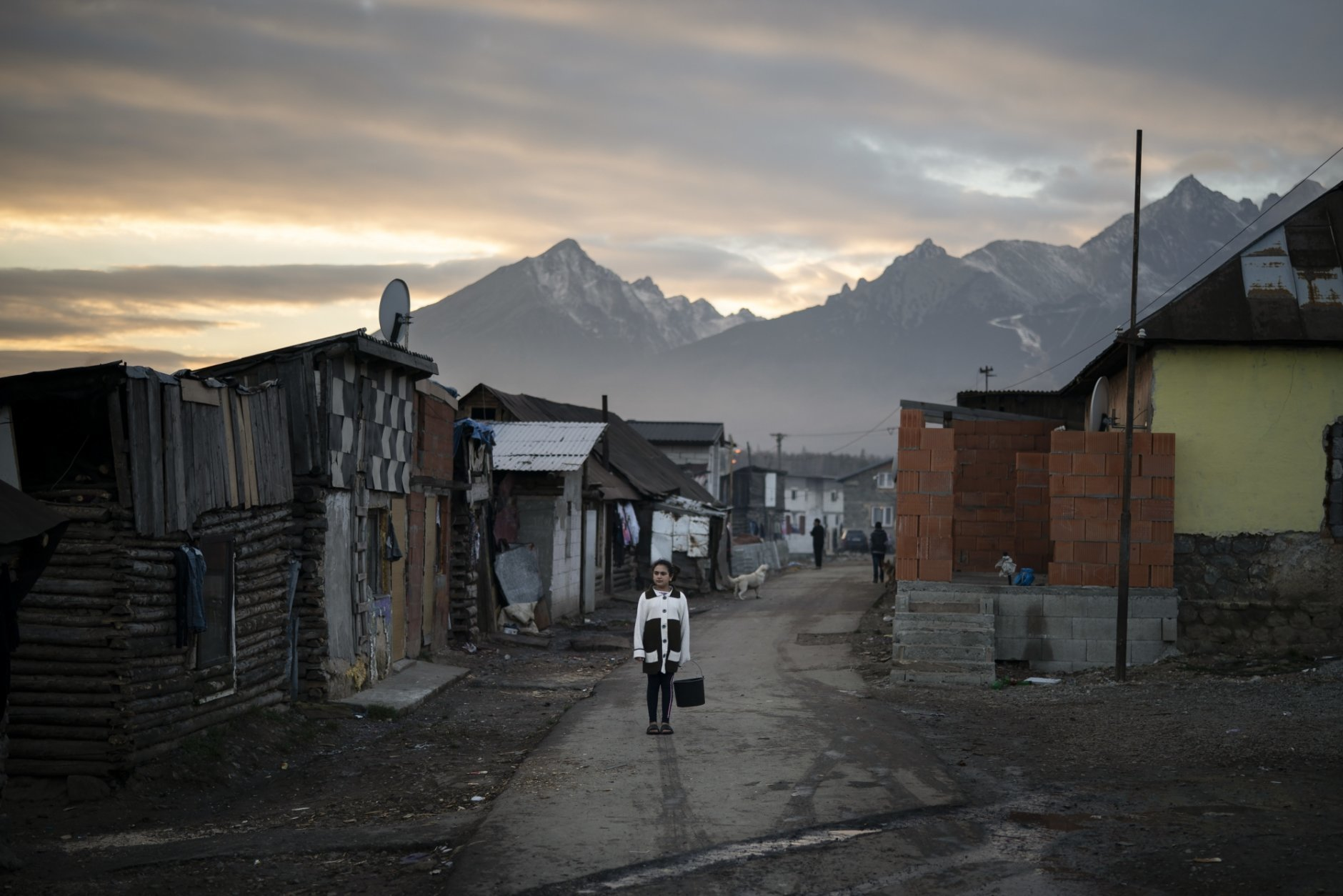 In this Nov. 16, 2018, photo, a Roma girl holds with a bucket to collect water in a village near Kezmarok, Slovakia. An investigation by The Associated Press has found that women and their newborns in Slovakia are routinely, unjustifiably and illegally detained in hospitals across the European Union country. Roma women, vulnerable to racist abuse and physical violence, suffer particularly.  They're also often poor, and mothers who leave hospitals before doctors grant permission forfeit their right to a significant government childbirth allowance of several hundred euros. (AP Photo/Felipe Dana)