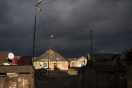 In this Nov. 14, 2018, photo, a Roma woman stands at the entrance of her house as dark clouds hover over the Podhorany village near Kezmarok, Slovakia. An investigation by The Associated Press has found that women and their newborns in Slovakia are routinely, unjustifiably and illegally detained in hospitals across the European Union country. Roma women, vulnerable to racist abuse and physical violence, suffer particularly.  They're also often poor, and mothers who leave hospitals before doctors grant permission forfeit their right to a significant government childbirth allowance of several hundred euros. (AP Photo/Felipe Dana)