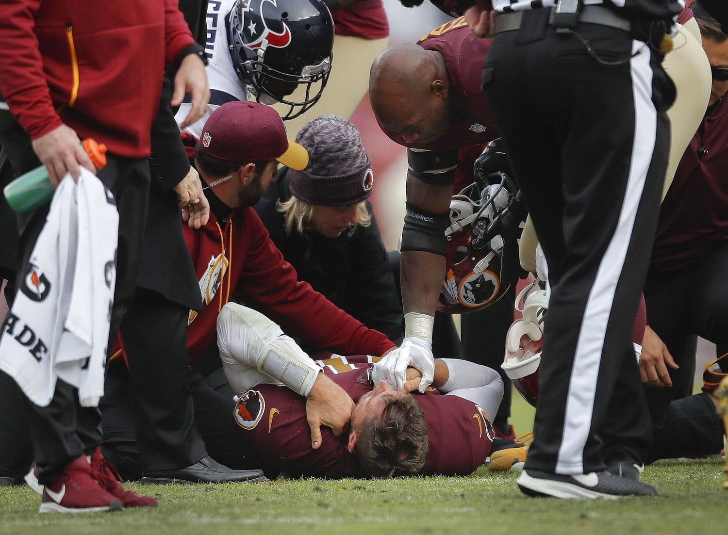 Washington Redskins quarterback Alex Smith (11) lays on the ground as teammate Adrian Peterson, right, holds his hand after an injury during the second half of an NFL football game against the Houston Texans, Sunday, Nov. 18, 2018 in Landover, Md. Smith broke his right tibia and fibula on a sack by Texans' Kareem Jackson. (AP Photo/Pablo Martinez Monsivais)