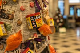 photo of a tree decorated with Old Bay tins, crabs and newspaper