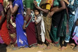 In this Dec. 5, 2018, file photo, a child waits in a queue for free food as thousands gather to mark Bhim Rao Ambedkar's death anniversary at Chaithyabhoomi in Mumbai, India. Ambedkar, an untouchable, was one of India's prominent freedom fighters and the chief architect of the Indian Constitution that outlawed discrimination based on caste. (AP Photo/Rajanish Kakade, File)