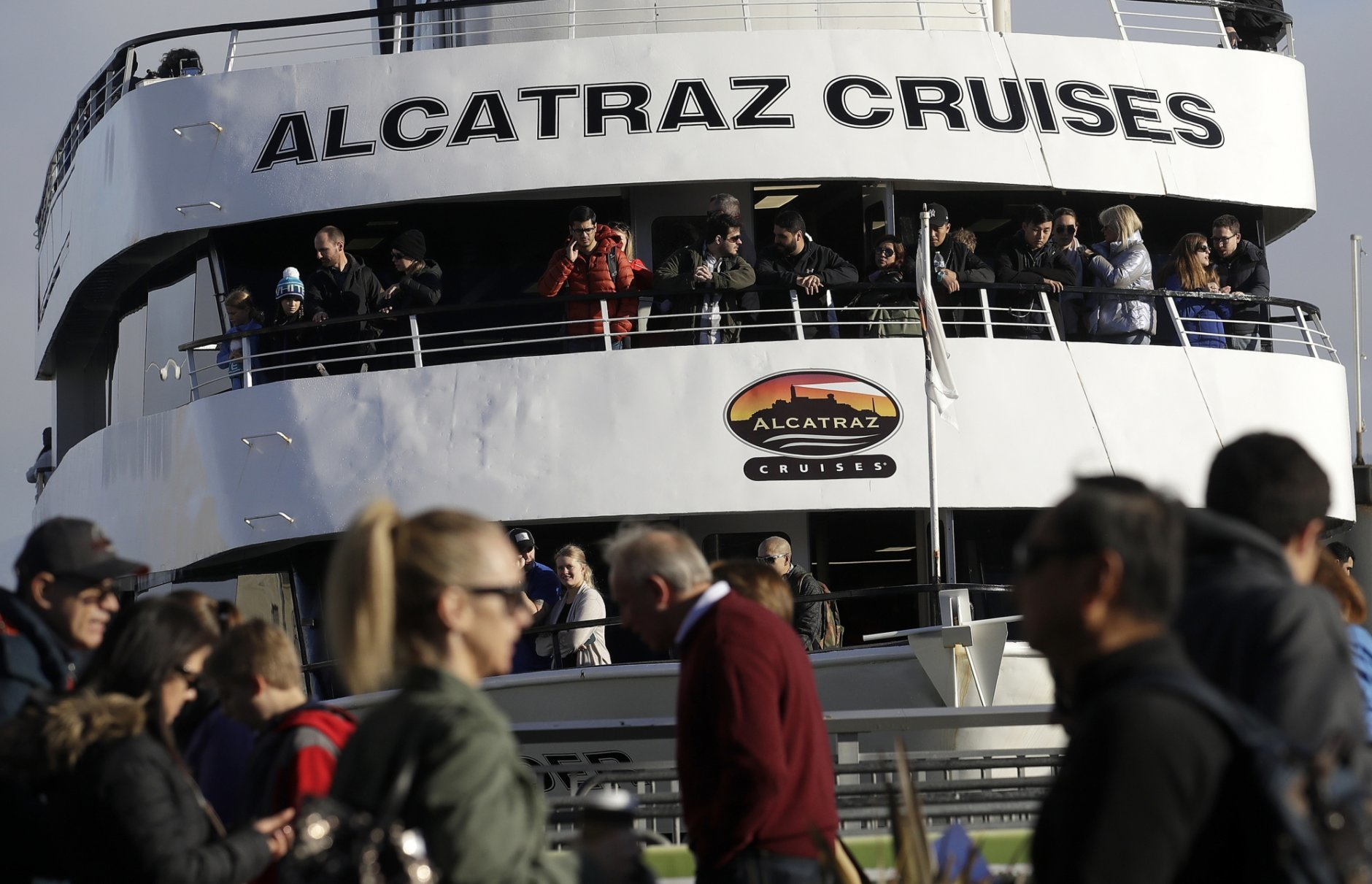 An Alcatraz Cruise ship waits to depart as customers stand in line for ferry service in San Francisco, Saturday, Dec. 22, 2018. A partial federal shutdown has been put in motion because of gridlock in Congress over funding for President Donald Trump's Mexican border wall. The company that provides ferry services to Alcatraz Island kept its daytime tours but canceled its behind-the-scenes and night tours for Saturday. (AP Photo/Jeff Chiu)