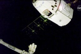 In this image taken from NASA Television, the SpaceX Dragon cargo spacecraft approaches the robotic arm for docking to the International Space Station, Saturday, Dec. 8, 2018. A communication drop-out has delayed a Christmas delivery at the International Space Station. (NASA TV via AP)