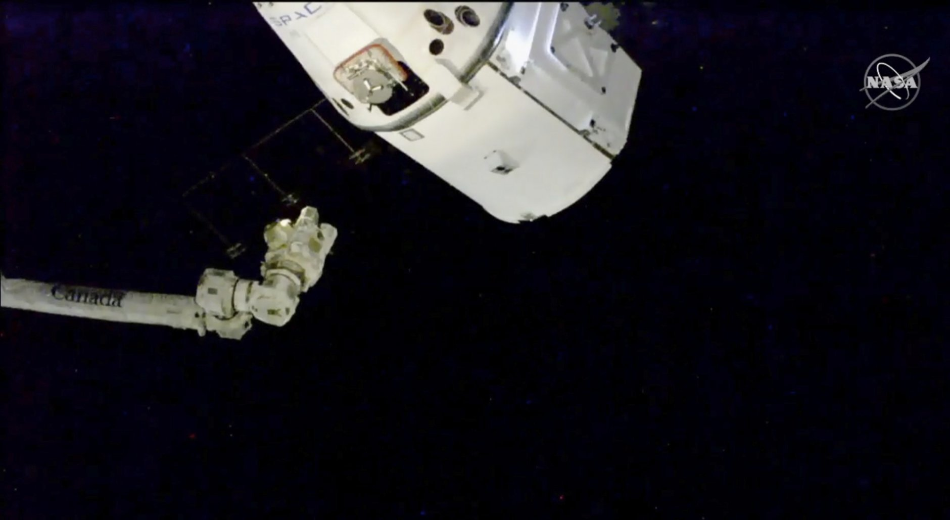 In this image taken from NASA Television, the SpaceX Dragon cargo spacecraft approaches robotic arm for docking to the International Space Station, Saturday, Dec. 8, 2018. A SpaceX delivery full of  Christmas goodies has arrived at the International Space Station. The Dragon capsule pulled up at the orbiting lab Saturday, three days after launching from Florida. (NASA TV via AP)