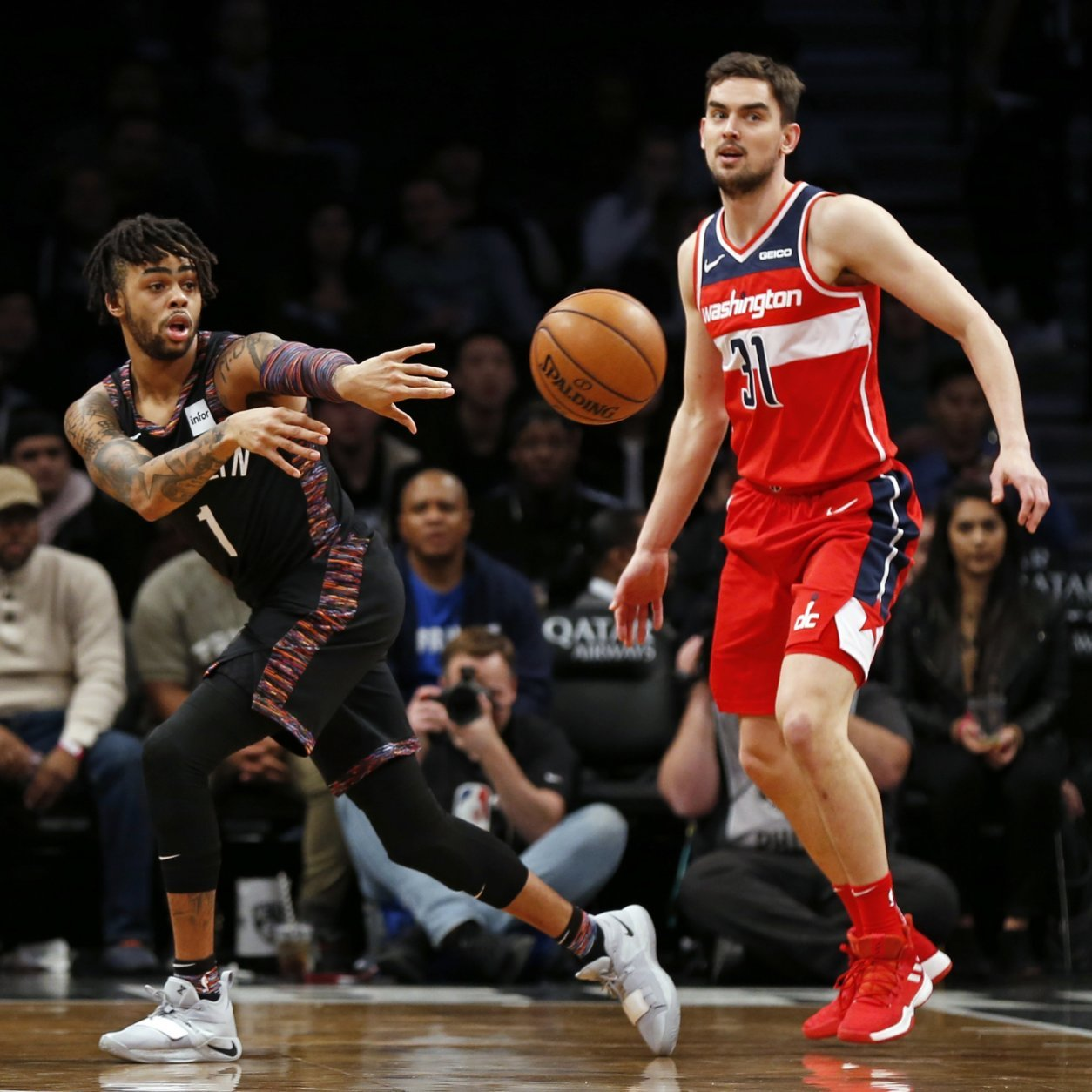 Brooklyn Nets guard D'Angelo Russell (1) passes around Washington Wizards guard Tomas Satoransky (31) during the first half of an NBA basketball game Friday, Dec. 14, 2018, in New York. (AP Photo/Adam Hunger)
