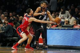 Brooklyn Nets guard Spencer Dinwiddie (8) looks to pass around Washington Wizards guard Tomas Satoransky during the first half of an NBA basketball game Friday, Dec. 14, 2018, in New York. (AP Photo/Adam Hunger)
