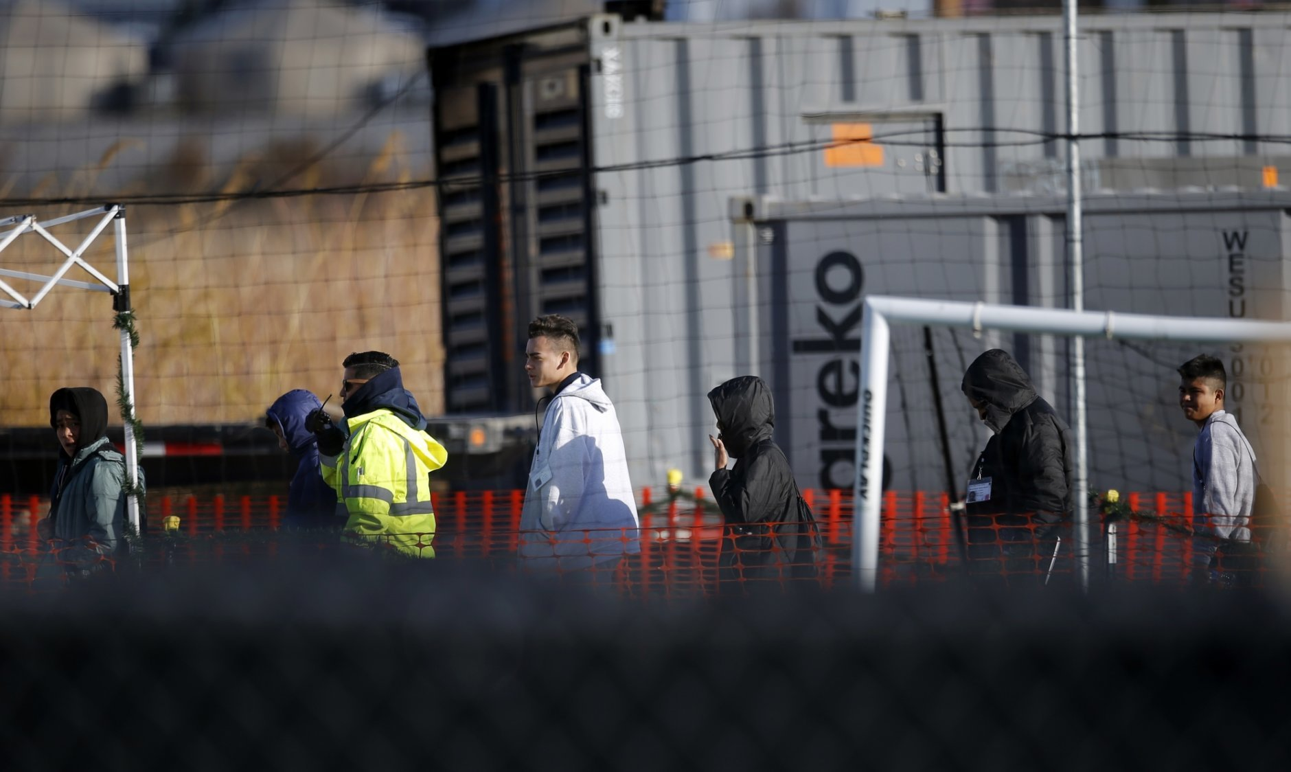 FILE - In this Thursday, Dec. 13, 2018 file photo, migrant teens walk inside the Tornillo detention camp in Tornillo, Texas. A zero-tolerance order from President Donald Trump resulted in more than 2,500 migrant children being separated from their families. (AP Photo/Andres Leighton)