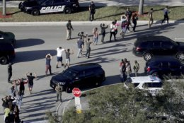 FILE - In this Wednesday, Feb. 14, 2018 file photo, students from Marjory Stoneman Douglas High School in Parkland, Fla., hold their hands in the air as they are evacuated by police after a shooter opened fire on the campus. The mass shooting which killed 17 students and staff, and sparked nationwide student-led marches for gun control _ was the top news story of 2018, according to The Associated Press' annual poll of U.S. editors and news directors. (Mike Stocker/South Florida Sun-Sentinel via AP)