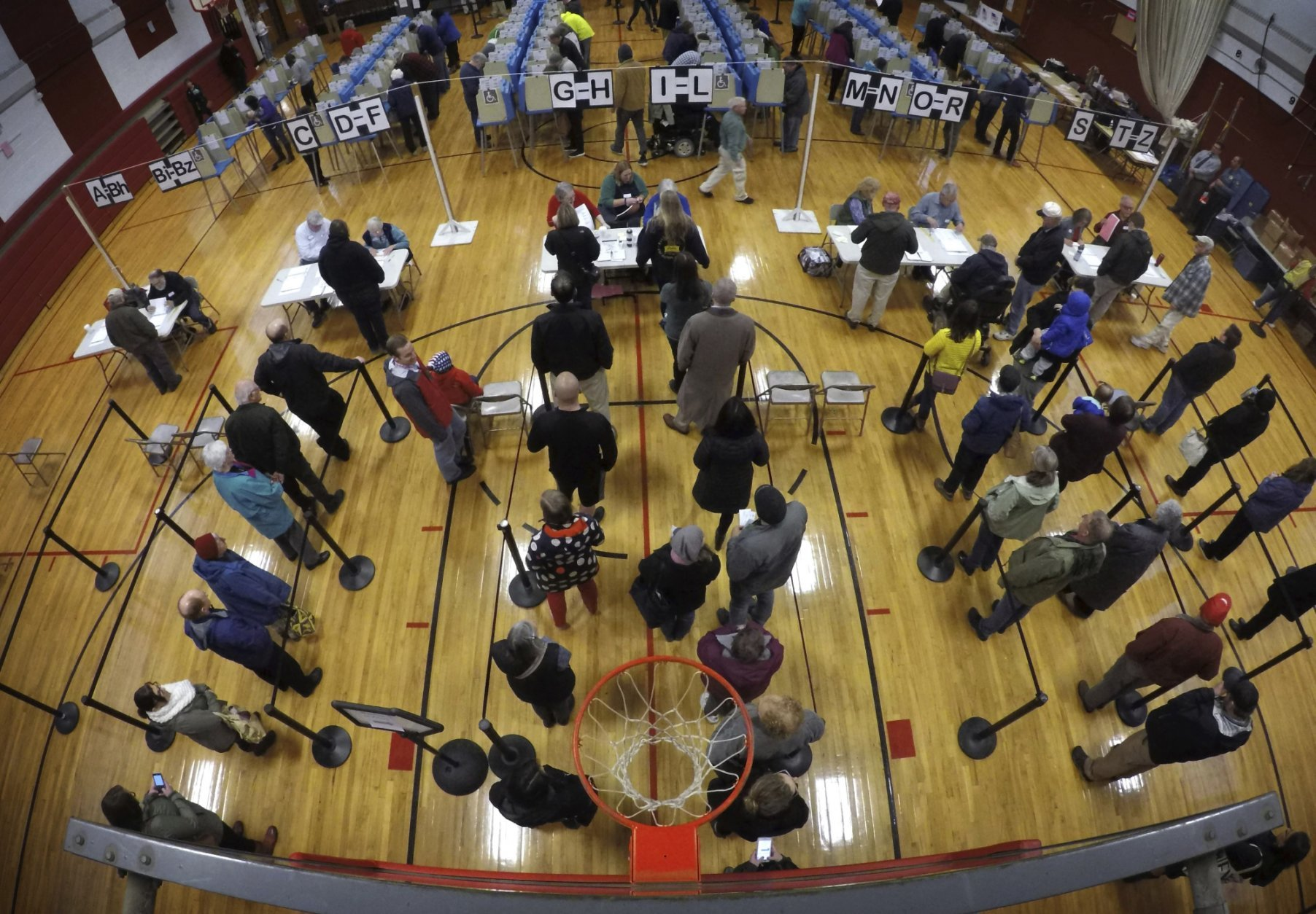 FILE - In this Tuesday, Nov. 6, 2018 file photo, voters wait in line in the gymnasium at Brunswick Junior High School to cast their ballots for the mid-term election in Brunswick, Maine. With Donald Trump on the minds of many voters, Democrats managed to flip about 40 seats in the House of Representatives to seize control of that chamber from Republicans. Democrats also flipped several governorships around the country. But the GOP boosted its slim majority in the Senate and will have a 53-47 edge in the next session of Congress. (AP Photo/Robert F. Bukaty)