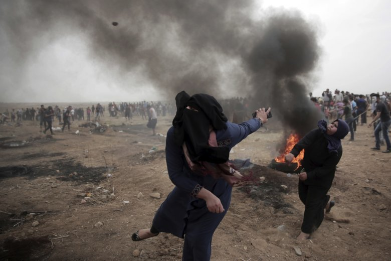 Palestinian women hurl stones at Israeli troops during a protest at the Gaza Strip's border with Israel