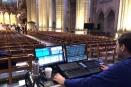 "Technicians sat in front of panels tweaking adjustments on keyboards that would shape countless elements of what viewers will see and hear during Wednesday's service along the aisles, pews and alter, which was labeled as ""stage."" (WTOP/Kristi King)"