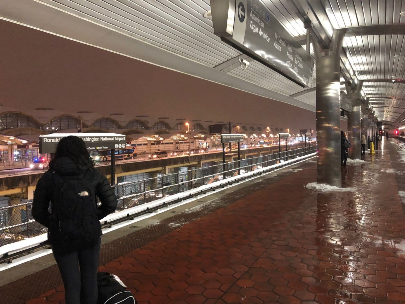 Travelers wait at the Metro station as snow falls Sunday around Reagan National Airport. (WTOP/Max Smith)