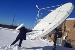 WTOP's Lisa Weiner clears the station satellite dish of snow. (WTOP/Jared Ruderman)
